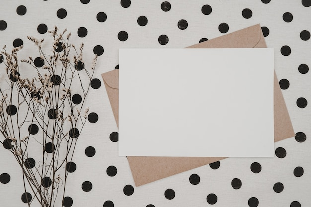 Blank white paper on brown paper envelope with limonium dry flower and carton box on white cloth with black dots. mock-up of horizontal blank greeting card.