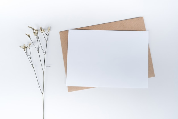 Blank white paper on brown paper envelope with limonium dry flower. top view of craft paper envelope on white background.