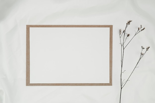 Blank white paper on brown paper envelope with limonium dry flower on white cloth. horizontal blank greeting card. top view of craft envelope on white background.