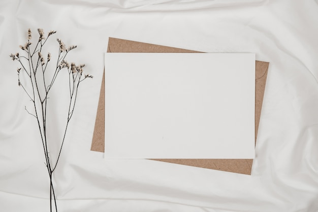 Blank white paper on brown paper envelope with limonium dry flower on white cloth