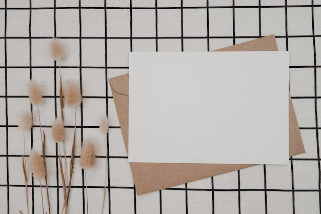 Blank white paper on brown paper envelope with rabbit tail dry flower and carton box on black cloth with black white grid pattern. mock-up of horizontal blank greeting card.