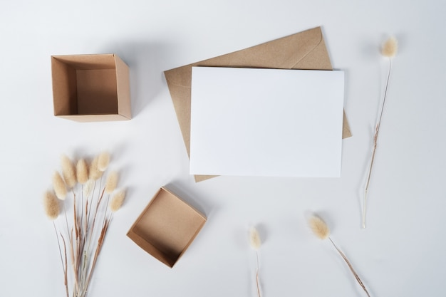 Blank white paper on brown paper envelope with rabbit tail dry flower and carton box. top view of craft  envelope on white background.