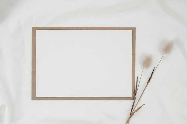 Blank white paper on brown paper envelope with rabbit tail dry flower on white cloth. horizontal blank greeting card. top view of craft envelope on white background