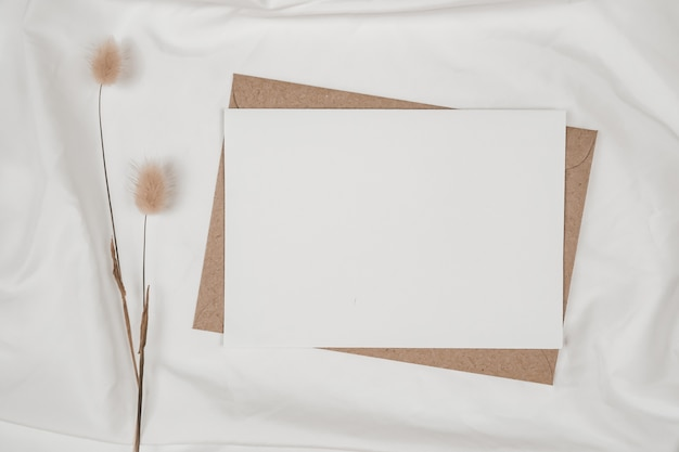 Blank white paper on brown paper envelope with rabbit tail dry flower on white cloth