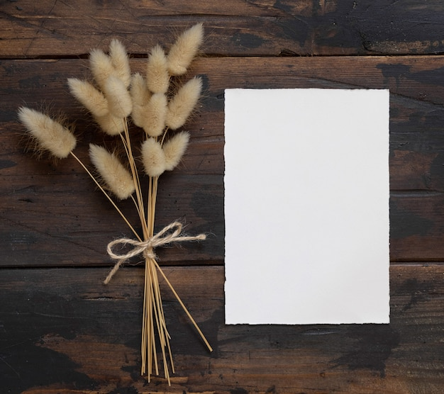 Blank white paper card on brown wooden table with dried flowers bouquet aside, top view. boho invitation card mockup