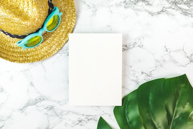 Blank white paper card on marble table with summer items