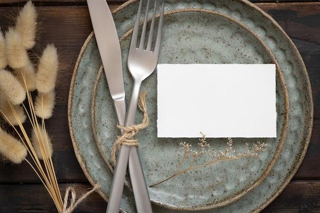 Пустая белая бумажная карточка на тарелке с вилкой и ножом на столе с богемным декором