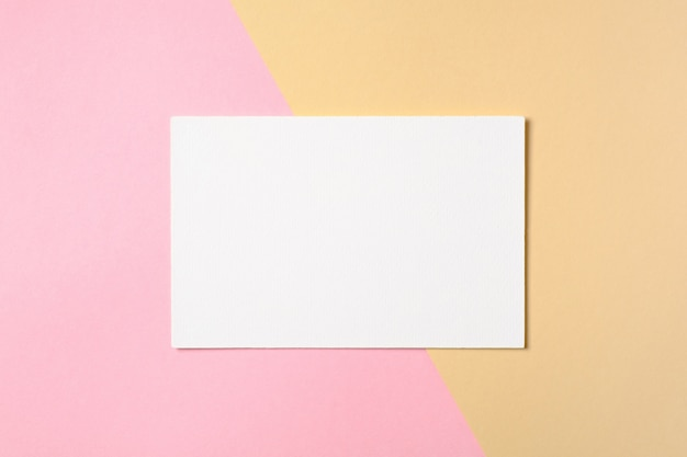 Blank white paper card on two color pastel pink and yellow background.