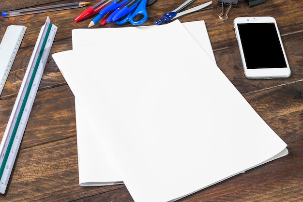 Blank white paper; cellphone and stationeries on wooden plank