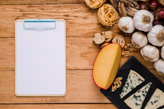 Blank white paper on clipboard near healthy ingredients on desk