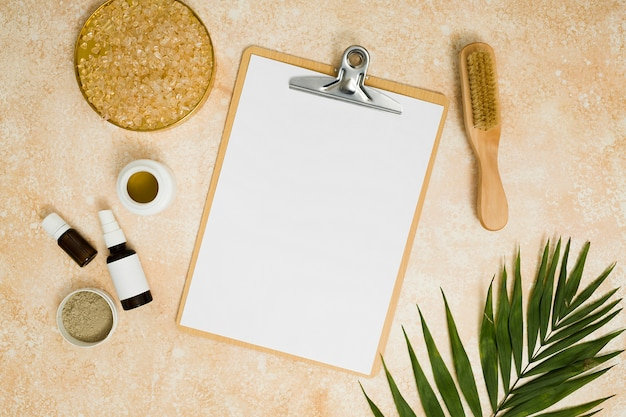 Blank white paper on clipboard surrounded with rhassoul clay; salt; honey; essential oils; brush and palm leaves