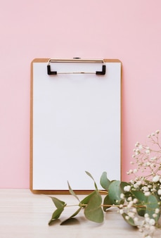 Blank white paper on clipboard with leaves and baby's-breath flowers on wooden desk against pink background