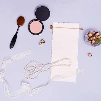 Blank white paper; dried pink rose bud in jar; ribbon; necklace; hairstick; oval brush; compact powder; golden hairpin and clutcher