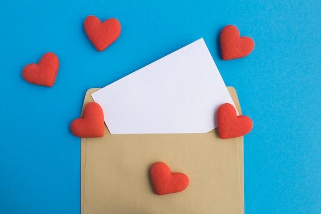青いテーブルのテキスト、封筒、赤いハート型のクッキー用の空白の白い紙。スペースをコピーします。上面図。