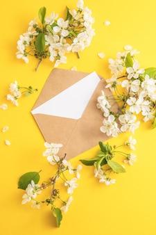 封筒の空白の白い紙と紙の色の背景にその周りの花