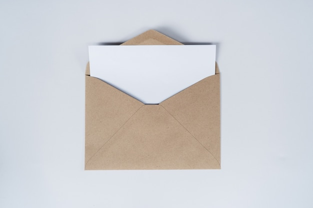 Blank white paper is placed on the open brown paper envelope. top view of craft paper envelope on white background.