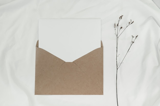 Blank white paper is placed on the open brown paper envelope with limonium dry flower on white cloth. top view of craft paper envelope on white background.