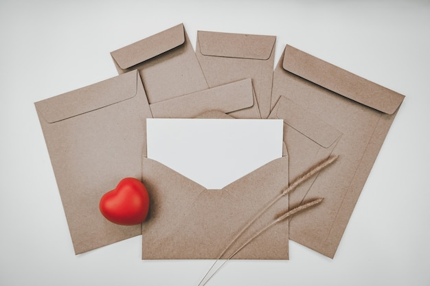 Blank white paper is placed on the open brown paper envelope with red heart and bristly foxtail dry flower