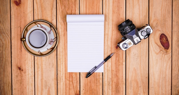 Blank white paper notes with coffee and old camera on top wood table
