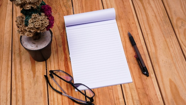 Blank white paper notes with edelweis flower and eyeglasses on top wood table