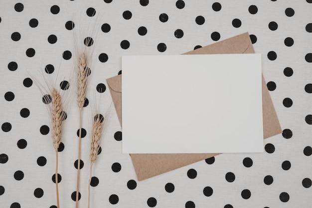 Чистый белый лист бумаги на коричневом бумажном конверте с сухим цветком ячменя и картонной коробке на белой ткани с черными точками