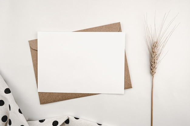 보리 마른 꽃과 검은 점이있는 흰색 천으로 갈색 종이 봉투에 빈 백서
