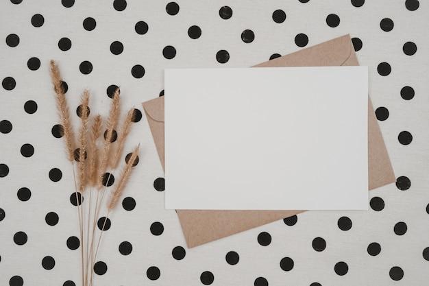 Чистый белый лист бумаги на коричневом бумажном конверте с сухим цветком щетинистого лисохвоста и картонной коробке на белой ткани с черными точками