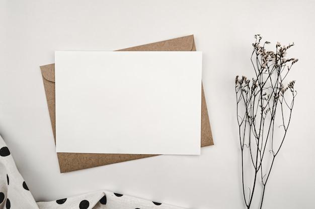 Limonium 마른 꽃과 검은 점이있는 흰색 천이있는 갈색 종이 봉투에 빈 백서