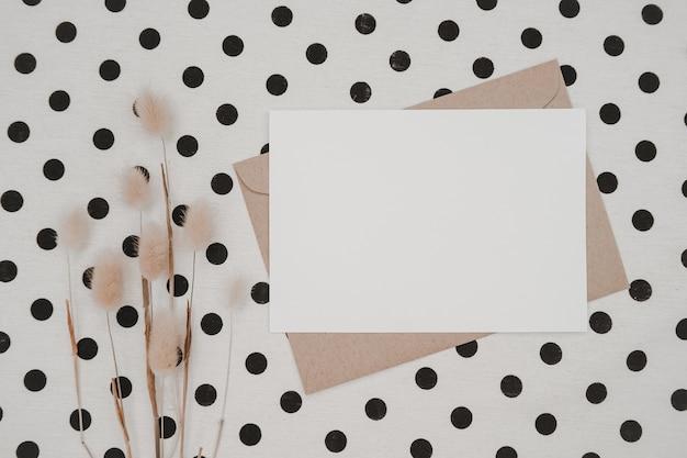 Пустая белая бумага на коричневом бумажном конверте с сухим цветком кроличьего хвоста и картонной коробкой на белой ткани с черными точками. макет горизонтальной пустой поздравительной открытки. вид сверху ремесленного конверта.