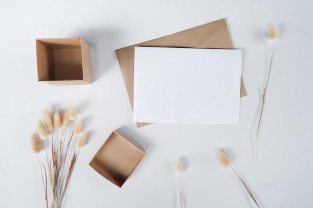 茶色の紙の封筒に空白の白い紙とウサギの尾のドライフラワーとカートンボックス。白い背景の上のクラフト封筒の平面図です。