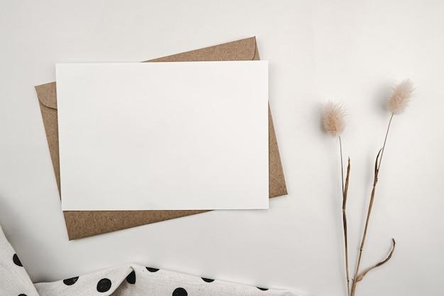 토끼 꼬리 마른 꽃과 검은 점이있는 흰색 천으로 갈색 종이 봉투에 빈 백서