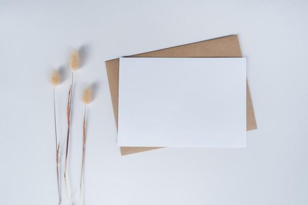 茶色の紙の封筒に空白の白い紙とウサギの尾のドライフラワー。白い背景の上のクラフト紙の封筒の平面図です。