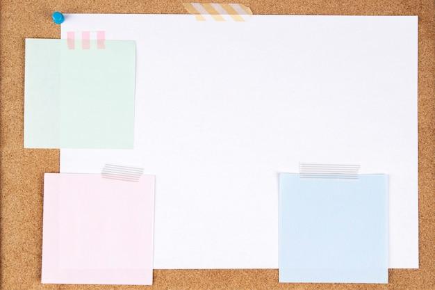 空白の白い紙のページとコルクボードの背景に粘着テープで添付されたメモ帳