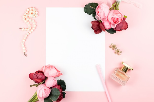 Blank white paper, pen, jewelry, perfume,  flowers on pastel background