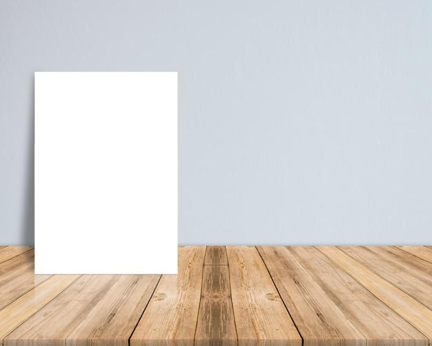 トロピカルな板の木製の床に白い紙のポスターを空にする。