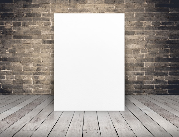 Blank white paper poster at grunge brick wall and wood plank floor