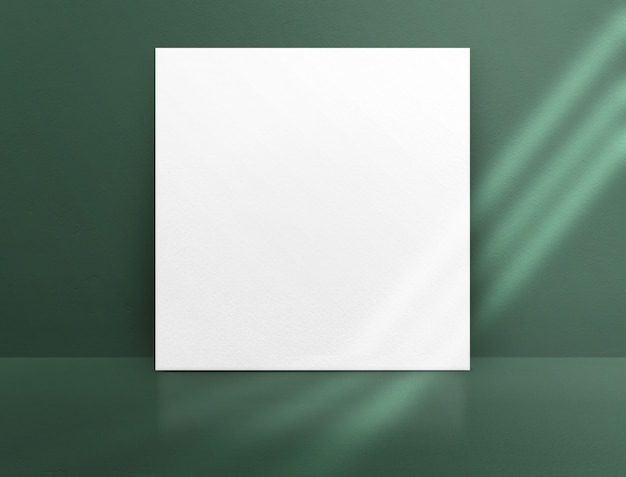 Blank white paper poster leaning at green color concrete wall and floor with window sunlight