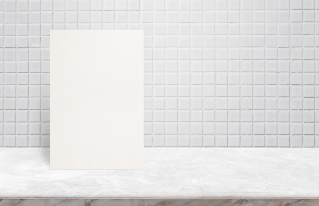 Blank white paper poster on marble stone table top at white mosaic ceramic tile wall