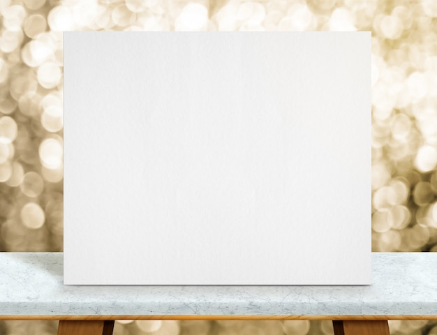 Blank white paper poster on marble table top and sparkling gold bokeh light