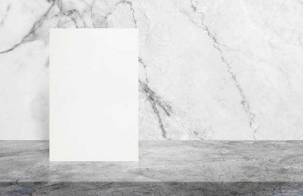 Blank white paper poster on polishing cement table top at white marble stone wall.