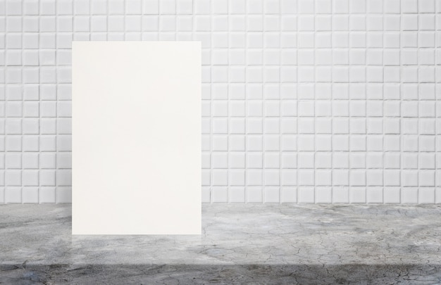 Blank white paper poster on polishing cement table top at white mosaic ceramic tile wall.
