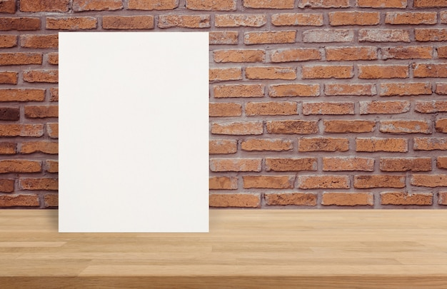 Blank white paper poster on wood table top at old brick wall,template mock up for adding your design.