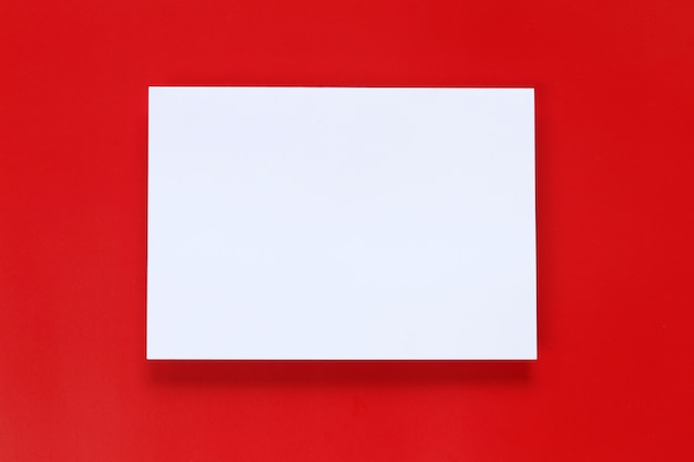 Blank white paper on a red art paper background.