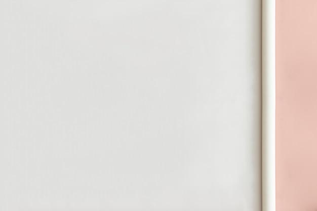 パステルピンクの背景に空白の白い紙ロール