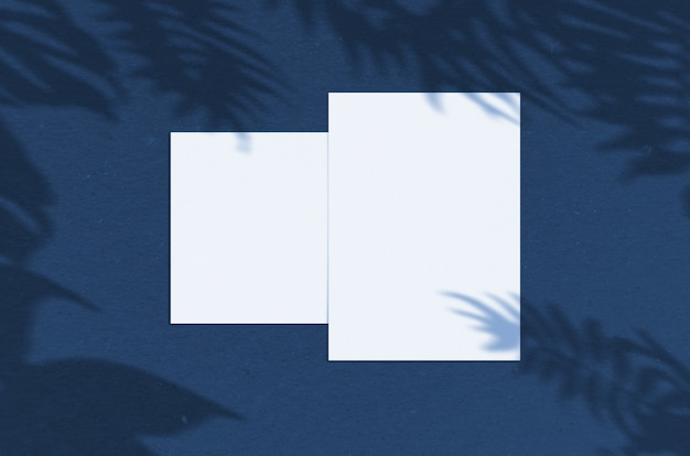 Blank white paper sheet 5x7 inches with palm shadow overlay. modern and stylish greeting card or wedding invitation mock up. color of the year 2020 classic blue