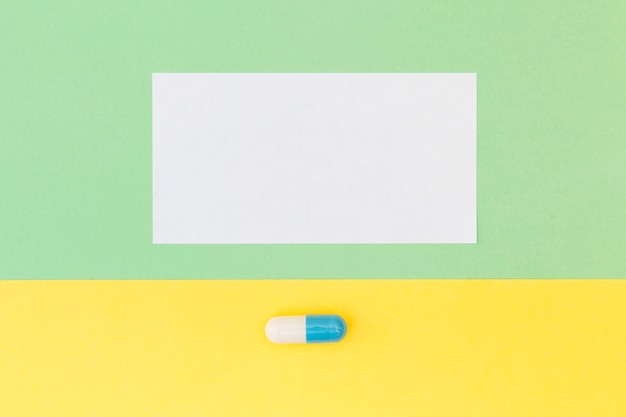 Blank white paper and single capsule on green and yellow background