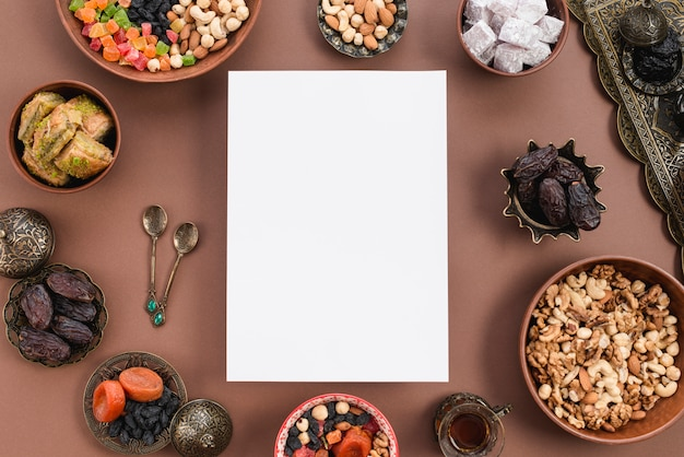 Blank white paper surrounded with circular dried fruits; nuts; lukum; baklava bowl on brown backdrop