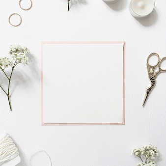 Blank white paper surrounded with rings; gypsophila; string; candles and scissor on white background