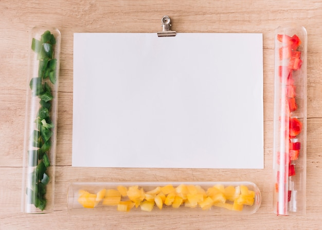 Blank white paper surrounded with transparent test tubes with slices of green; yellow and red bell peppers
