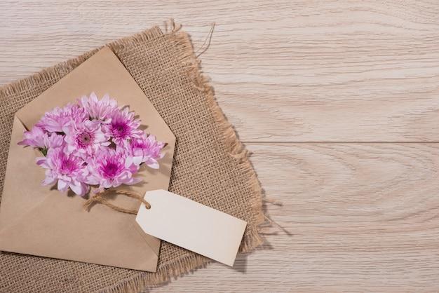 木製のテーブルに茶色の封筒とピンクの花と空白の白い紙のタグ。